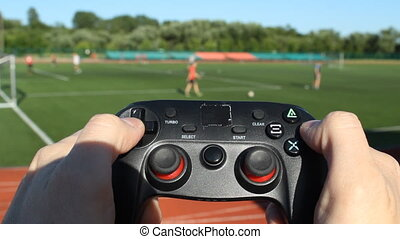 A man with a game joystick playing football, in the...