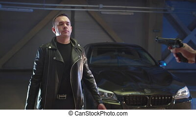 A gun is pointed at a guy in a leather jacket. He raises his hands