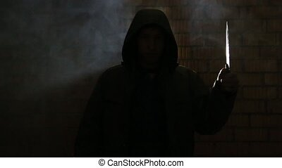 A man with a knife in a dark smoky room - Teen in the hood...