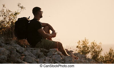 A man with a large backpack is sitting on the mountain at sunset