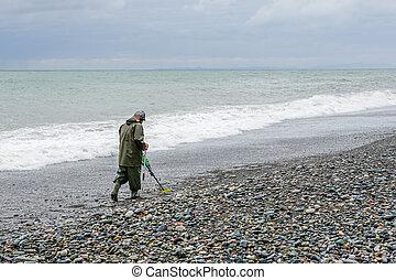 A man with a metal detector walks along the beach of the Black Sea, treasure hunter