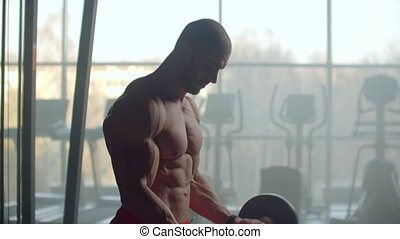 A man with a naked torso and a pumped strong body and relief muscles of the press raises a barbell with a weight on the background of the window training his hands.