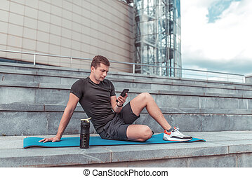 A man with a phone, in the summer on a training session in the city, fitness on the street, writes a message on a smartphone, an online application on the phone, a shaker with water and protein.