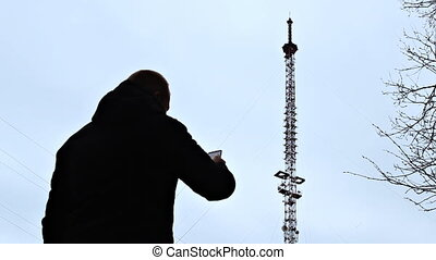 A man with a phone is standing by the telephone tower...