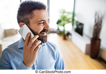 A man with a smartphone making a phone call at home.
