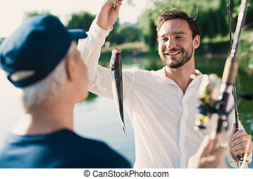 A man with a spinning in his hands brags at the old man, who is ahead of him with the fish he just caught