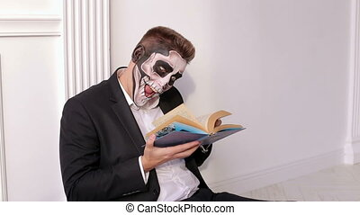 A man with a terrible make-up in form of a skull is holding...
