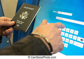 A man with a US passport and boarding pass fills the electronic form of self-registration on the flight
