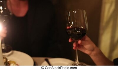 A man with a woman drinking wine in a restaurant by candlelght