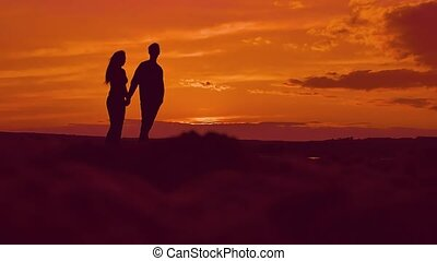 a man with a woman holding hands silhouette slow motion video