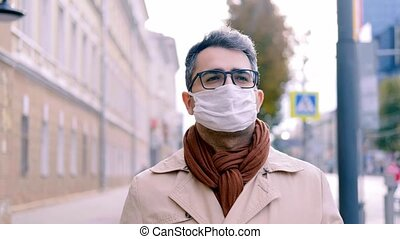 A man with an Oriental appearance in a mask walks down the street along the sidewalk along the road. Protecting health in the context of the covid-19 coronavirus epidemic