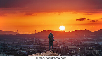 a man with backpack standing on the mountain enjoying beautiful sunset view in Osaka city, Japan. Travelling and adventuring in Asia