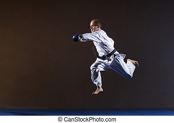 A man with blue overlays on his hands strikes with a hand in a jump