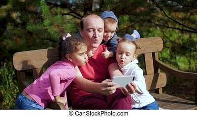 A man with children photographed on a smartphone sitting on a bench. Happy family taking selfie in the park. Family video call on mobile Internet. 4k 60fps slow motion.