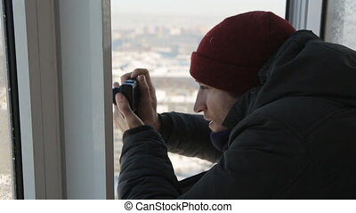 A man with compact camera takes pictures of the winter city from the window from a height
