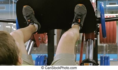 A man with excess weight doing leg presses on the simulator...