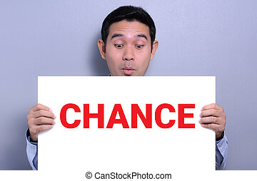 A man with excited face  showing CHANCE word on the paper