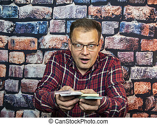 A man with glasses is surprised at the money in his hands.
