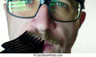 A man with glasses shaves his mustache trimmer