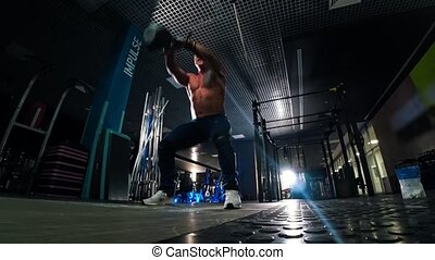 A man with gray hair bodybuilder pulls a kettlebell in the ...