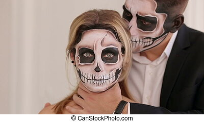 A man with Halloween makeup is holding his girlfriend by the neck.