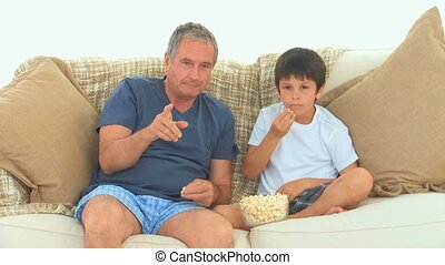 A man with his grandson watching a match on the tv