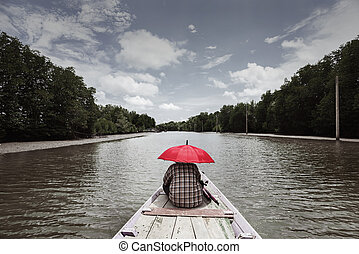 prow - A man with red umbrella sit at prow of boat in ...