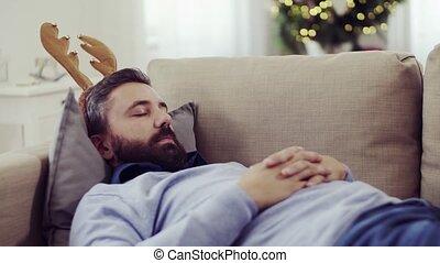 A man with reindeer headband lying on a sofa at Christmas...