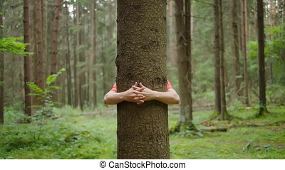 Man with strong hands hugs a tree trunk, nature conservation, environmental protection, unity with nature