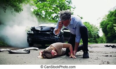 A man with telephone helping a young woman lying on the road after a car accident.