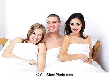 A man with two hot girls - Smiling man in bed between two...