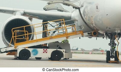 A man worker connects a transportable escalator for luggage...