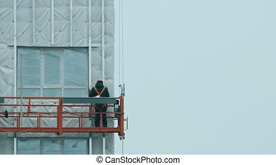 A man worker lifting up on the building for continue constructing. Mid shot