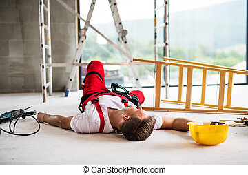 A man worker lying on the floor after an accident at the construction site.