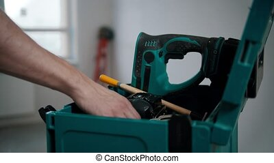 A man worker pulling a hammer out of the case