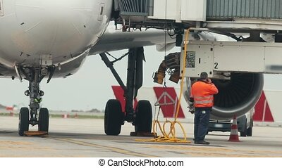 A man worker standing under the plane and talking on his phone