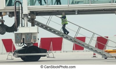 A man worker walking upstairs. Silhouettes of people going aboard through the glass passage to the airplane