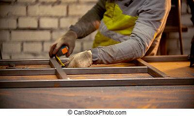A man worker welding the seams between the metal beams