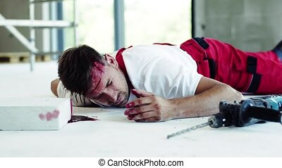 A man worker with bleeding wound on head lying on the floor...
