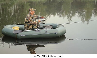 A man working at a laptop on the lake. A fisherman with a fishing rod