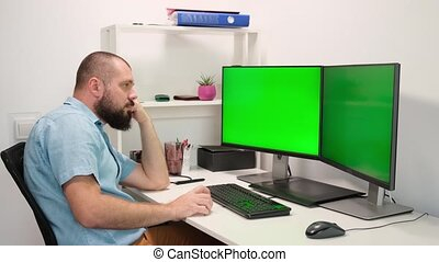 a man working at home in front of two green monitors. a man thinks and he has an idea. remote work. employee emotions