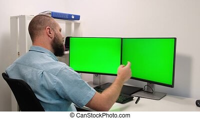a man working at home in front of two green monitors. the man is happy with the result. remote work. employee emotions