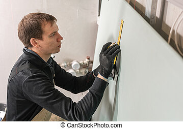A man working Builder makes a marking on the drywall for electrical wiring. Metal drywall construction in a house during renovation.