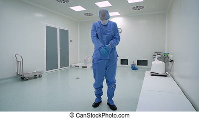 A man working in a clean room, pharmaceutical enterprise. Specialist in a protective suit, gloves, glasses and a mask.