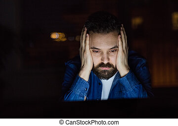 A man working on a laptop at home at night.