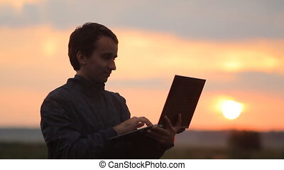 A man working on a laptop. Beautiful sunset on the background