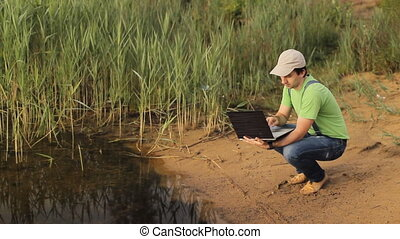 A man working on a laptop computer at the coast