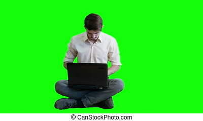 A man  working on a laptop while sitting on a background of a