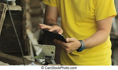 A man working on a tablet, puts aside tablet and begins...