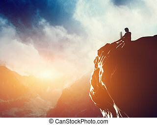 A man working on laptop sitting on the peak of a mountain at sunset.